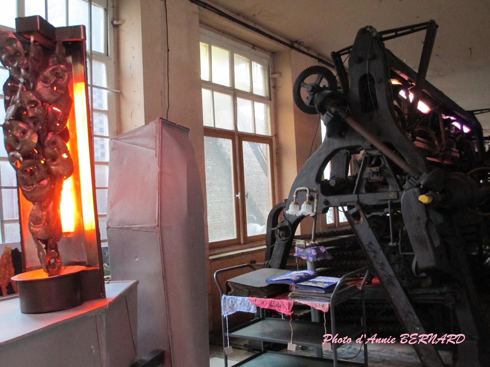 Une lampe et derrière un ancien métier à tulle